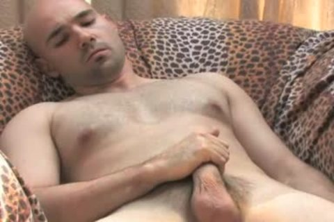 Bald hunk plays with his pecker